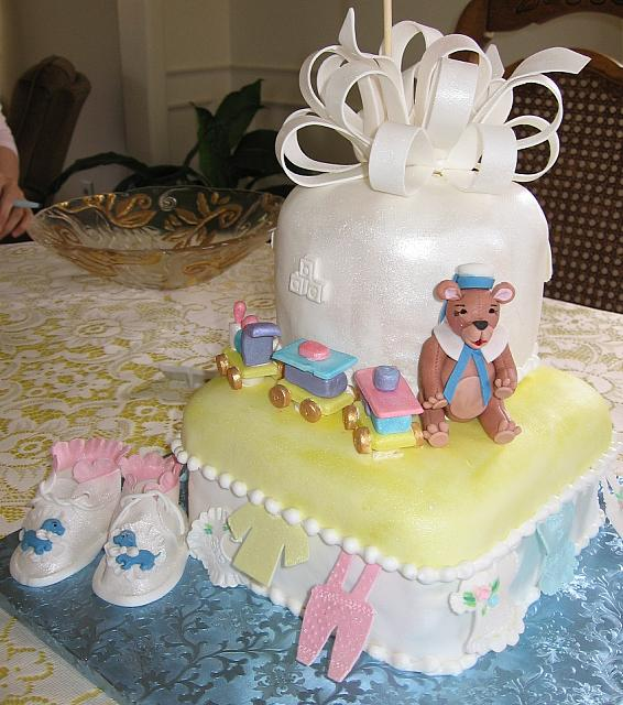Close up of the baby shower cake with baby shoes