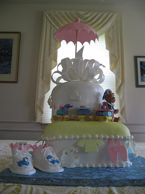 Baby Shower Cake with edible baby shoes, teddy bear, train, baby clothes, fancy bow, and umbrella.