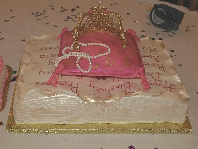 Princess themed cake of fondant covered antique book, edible pillow, and sugarpaste golden crown for baby girl -back view
