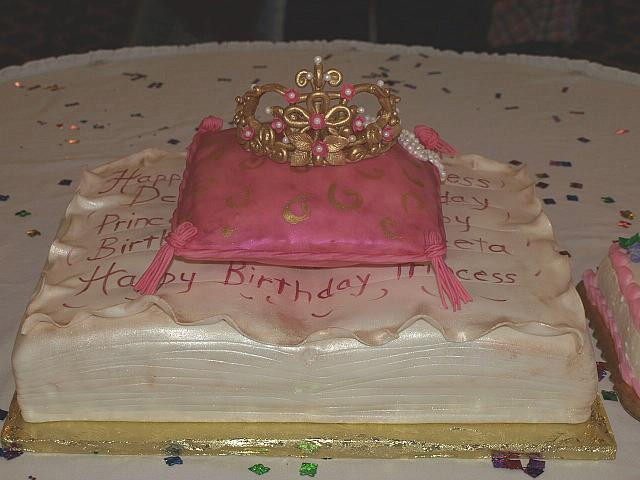 Princess themed cake of fondant covered antique book, edible pillow, and sugarpaste golden crown for baby girl -front view