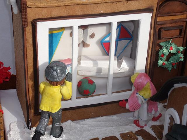 close up of toy shop window with a boy and girl gumpaste figurines looking in