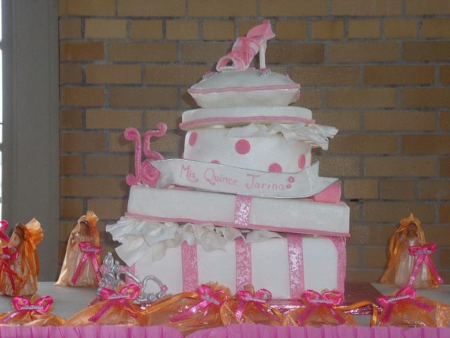 Quinceanera Cake in Pink and White with Stacked Presents, Edible Fashion Shoe, Pillow, and Princess Crown front view