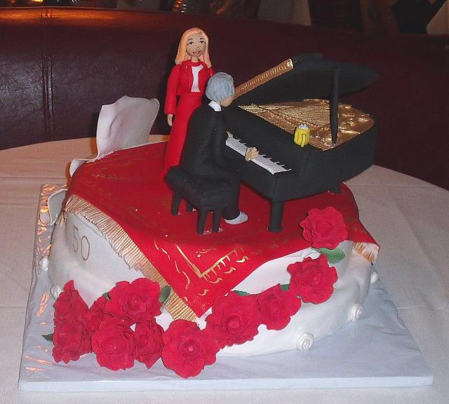 50th Anniversary Cake Couple On Oriental Rug next to Edible Grand Piano
