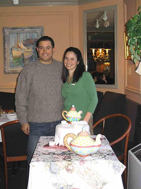 Engaged couple next to their bridal shower cake