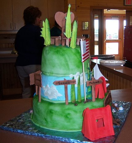 View of back of cake which had rustic signs labeled with camp names.