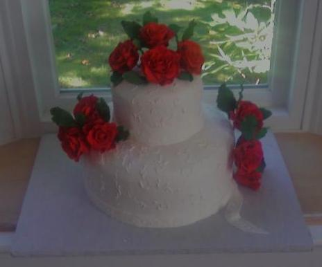 Angle view of red roses on white cake.