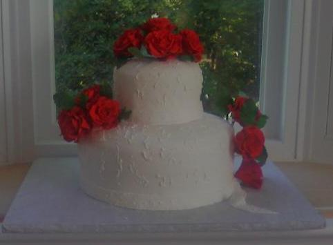 Front view of Red Roses On white fondant covered cake