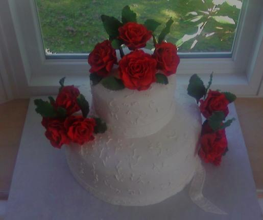 Here are edible, handmade Red Roses on top of two tiered white cake.  The cake has delicate scroll work from royal icing.  there are a dozen red roses.