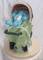 Old fashioned or old time baby carriage with blue gumpaste baby elephant inside