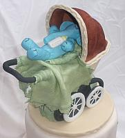 Old fashioned or old time baby carriage with blue gumpaste baby elephant side view
