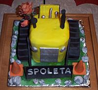 Bulldozer Cake front view, cake covered in fondant. Cake complete with orange gumpaste construction cones, gumpaste rocks, and gumpaste flowers