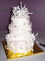 Fondant covered white whimsical cake with white gumpaste/sugarpaste edible decorations