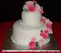 fondant covered wedding cake with multicolored pink sugarpaste roses cascade and edible pearl necklace fondant border